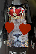 Lionheart theme in a fashionable shop window in central London. Obscuring the eyes of the lion, printed on a ladies' top, we see two hearts in red, the same colour as the crown on the top of its fury head.