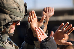 Lt. Col. Alan Kelly, commander of the 1st Infantry, 17th Regiment, signs his autograph on the hands of children while patrolling western Mosul, Iraq, Dec. 14, 2005. This is part of an effort to provide security in preparation for Iraq's first post-Saddam parliamentary elections. The western sector is home to Mosul's primarily Sunni population, which has been resistant to the American presence in Iraq.