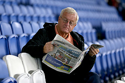 A fan in the stands reads through a newspaper prior to the match kick off