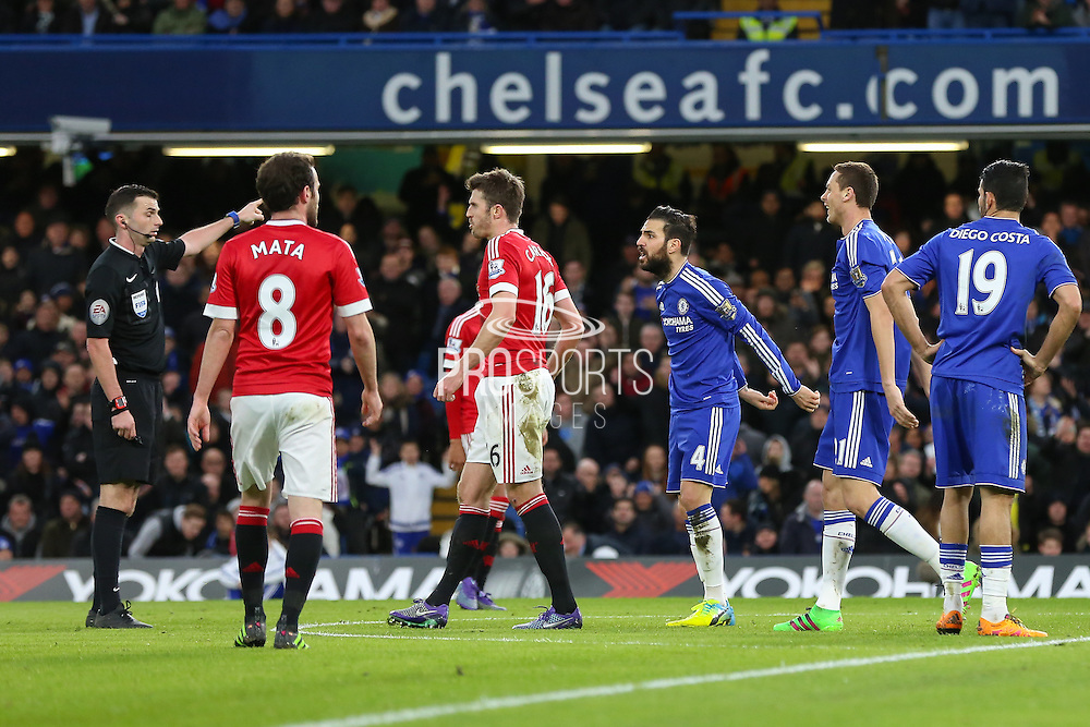Referee Michael Oliver gives a decision but Chelsea's Cesc Fabregas disputes during the Barclays Premier League match between Chelsea and Manchester United at Stamford Bridge, London, England on 7 February 2016. Photo by Phil Duncan.