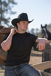 cowboy on a ranch with a saddle over his shoulder