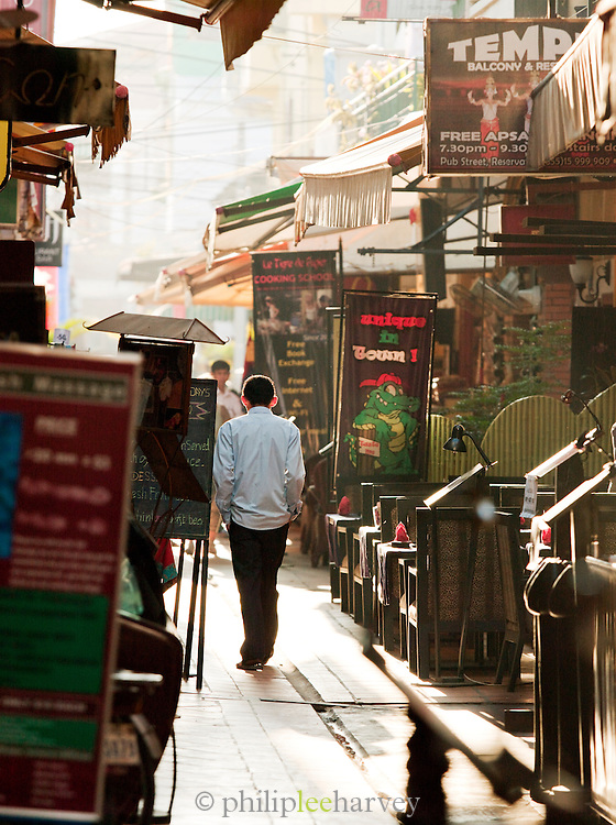A local man walking down a street cluttered with restaurants in the town of Siem Reap, Cambodia