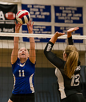 Interlakes Delaney Smith tips the ball over the net with Prospect Mountain's Catie Leberman during NHIAA Division III volleyball on Monday evening.  (Karen Bobotas/for the Laconia Daily Sun)