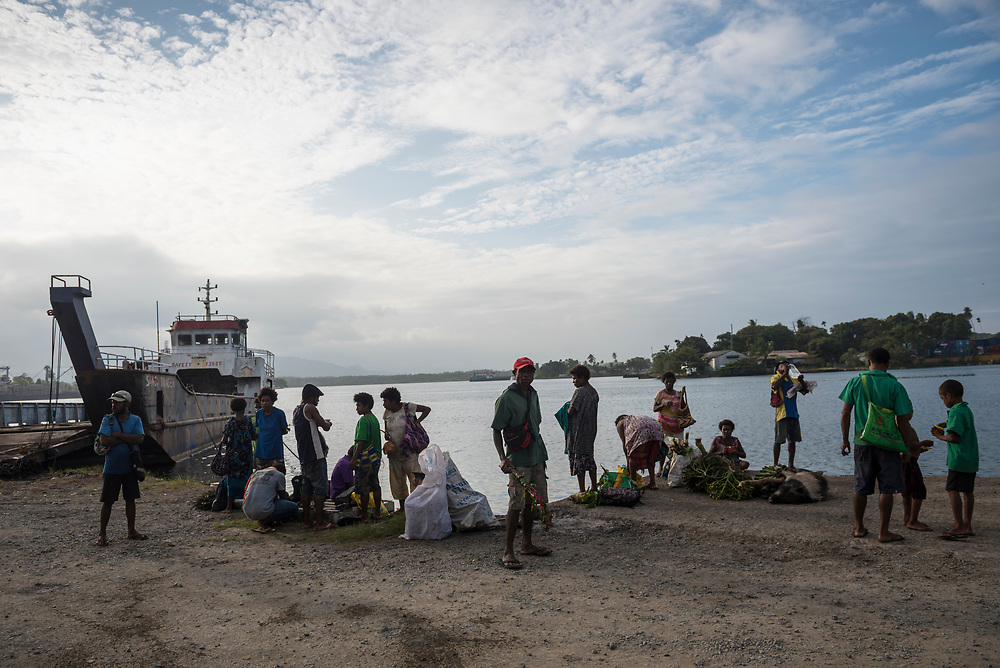 Passengers who traveled to Madang from Karkar Island stand beside the harbor after disembarking a small vessel, a copra boat (not pictured), in Madang, Papua New Guinea. The journey took about five hours.