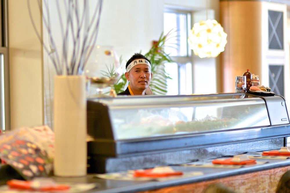 Chef behind the sushi bar at Cilantro Thai & Sushi Restaurant.