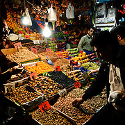 Customers help themselves to an assortment of nuts and dried fruits at a shop next to the Spice Bazaar (also known as the Egyption Bazaar) in Istanbul, Turkey.