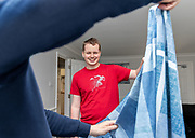 Support worker with service user folding laundry. <br /> Client  - Allerton, an integrated social care, housing, and development company.