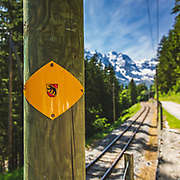 Railway to Murren in the Bernese Oberland, Switzerland with the ever-present Bernese bear and views to the dramatic chain of peaks from Breithorn running across to the Eiger and Jungfrau