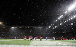 General view of the action as the snow falls during the Emirates FA Cup, quarter final match at Old Trafford, Manchester.
