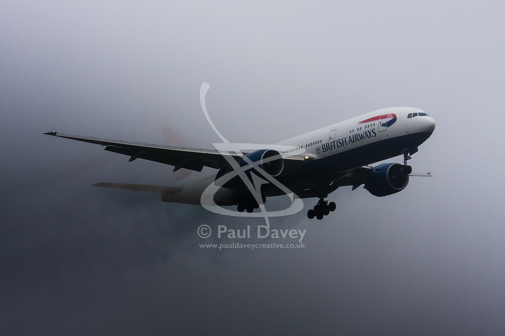 """January 3rd 2015, Heathrow Airport, London. Low cloud and rain provide ideal conditions to observe wake vortexes and """"fluffing"""" as moisture condenses over the wings of landing aircraft. With the runway visible only at the last minute, several planes had to perform a """"go-round"""", abandoning their first attempts to land. PICTURED: A British Airways Boeing 777 emerges from the low cloud, streaming water vapour, moments before touching down on Heathrow Airport's runway 27L"""