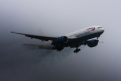 "January 3rd 2015, Heathrow Airport, London. Low cloud and rain provide ideal conditions to observe wake vortexes and ""fluffing"" as moisture condenses over the wings of landing aircraft. With the runway visible only at the last minute, several planes had to perform a ""go-round"", abandoning their first attempts to land. PICTURED: A British Airways Boeing 777 emerges from the low cloud, streaming water vapour, moments before touching down on Heathrow Airport's runway 27L"