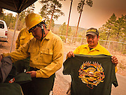 02 JUNE 2011 - ALPINE, AZ: Navajo Scouts Camp Crew Ervin Begay (FAR RIGHT BASEBALL HAT) and Harold Jones (HARD HAT) buy tee shirts at the Wallow Fire near Alpine. High winds and temperatures complicated firefighters' efforts to get the blaze under control. Officials have issued a preliminary evacuation order warning residents to be ready to move in the next 12 hours.   PHOTO BY JACK KURTZ