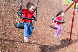 Young girls swinging on playground swings,