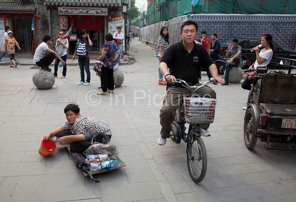 Beggar on Yandaixiejie Street (meaning Tobacco Pipe Lane) in Beijing, China. Located near to Houhai in downtown Beijing, Yandai Xiejie Street is a Hutong which attracts many tourists at day and night to it's souvenir shops and towards the bar area it leads to.