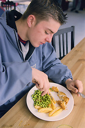 Young man eating lunch in café area of day centre for homeless and vulnerably housed young people,