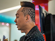 24 JULY 2013 - BANGKOK, THAILAND:  A hair stylist talks to potential customers at the Hairworld Festival in Siam Paragon, an upscale shopping mall in Bangkok, Thailand.        PHOTO BY JACK KURTZ