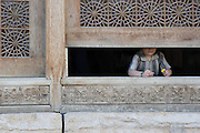 A boy in the opening of a finely carved window in the Arg (citadel) of Karim.Khan, Shiraz, the home of Persian romantics and poets. Shiraz, Iran, 2008