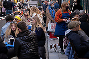 On the day that the UK government eased Covid restrictions to allow non-essential businesses such as shops, pubs, bars, gyms and hairdressers to re-open, drinkers enjoy warm afternoon sunshine at a busy bar outdoor serving drinks in Soho, on 12th April 2021, in London, England.