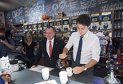 Liberal leader Justin Trudeau pours coffee for supporters next to local candidate Pierre Breton during a campaign stop at a coffee shop in Granby, Que., on October 6, 2015. The newly struck North American trade agreement will allow more American dairy products to enter Canada and, while it has yet to be ratified, it's already putting at least one MP from the governing Liberals in an awkward spot. THE CANADIAN PRESS/Paul Chiasson
