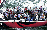 ALINGHI'S SKIPPER RUSSELL COUTTS WITH ONE HAND STEERING AND THE OTHER ON A BOTTLE OF CHAMPAGNE AS THEY NOW TAKE HOME THE AMERICA'S CUP.