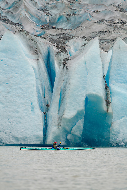 Sea kayak guide Corey Denton paddling in Mendenhall Lake near Juneau, Alaska with Mendenhall Glacier in the background. Photo © Robert Zaleski / rzcreative.com<br /> —<br /> To license this image contact: robert@rzcreative.com