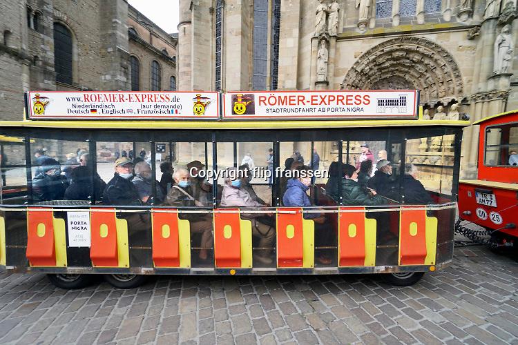 Duitsland, Trier, 26-9-2020 Een toeristentreintje, treintje met toeristen, rijdt langs de dom van deze stad in Rheinland Pfalz. De passagiers dragen allemaal een mondmasker tegen de verspreiding van het coronavirus . In Duitsland hanteert de overheid een strenger mondkapjesbeleid als in Nederland . Foto: ANP/ Hollandse Hoogte/ Flip Franssen