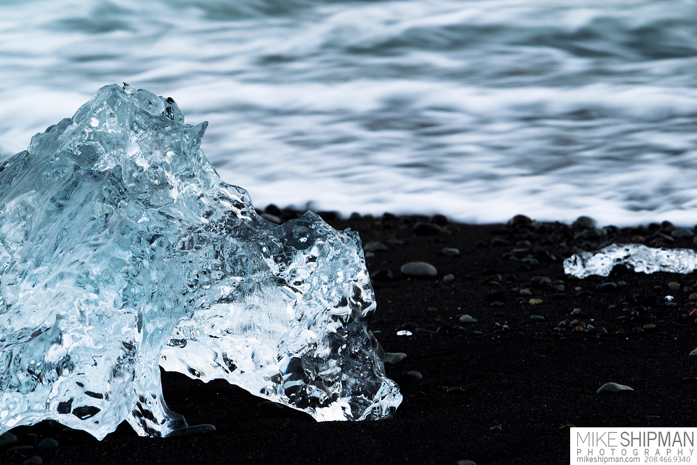 Clear iceberg chunk on the black sand beach of Jokulsarlon, Iceland