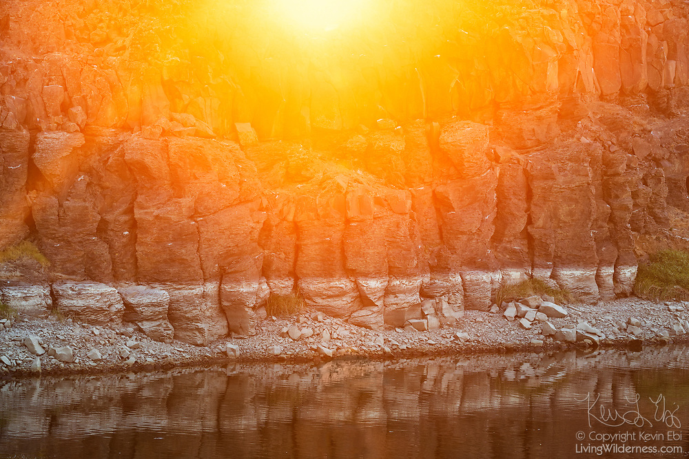 The sun rises over the edge of a basalt cliff that lines the Potholes Canal near Soda Lake in the Columbia National Wildlife Refuge in Washington state.