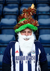 A West Bromwich Albion fan wears a festive hat and beard whilst attending the match