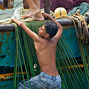 Climbing aboard a fishing boat: for now it's just for fun, but for many around this age it's to leave Egypt behind them.