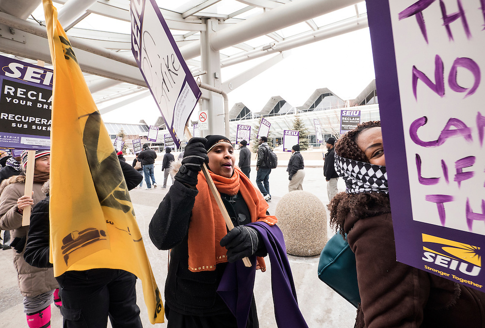 Randa Jama, center (orange scarf), who is a wheelchair assistant, came to support Twin Cities janitors represented by Service Employees International Union during a picket for a wage increase at Minneapolis-St. Paul International Airport's Terminal 1 February 17, 2016.  The union is asking for $15 for both full and part-time workers.
