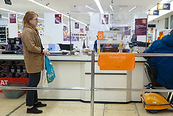 © Licensed to London News Pictures. 05/05/2020. London, UK. A shopper at a checkout at Sainsbury's supermarket. <br /> Partitions are installed in-between checkouts at Sainsbury's supermarket in north London to maintain the 2m distance rule to avoid the spread of COVID-19.  Photo credit: Dinendra Haria/LNP