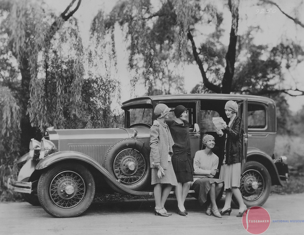 A quartet of young ladies stand near a 1928 Studebaker Commander Regal Sedan