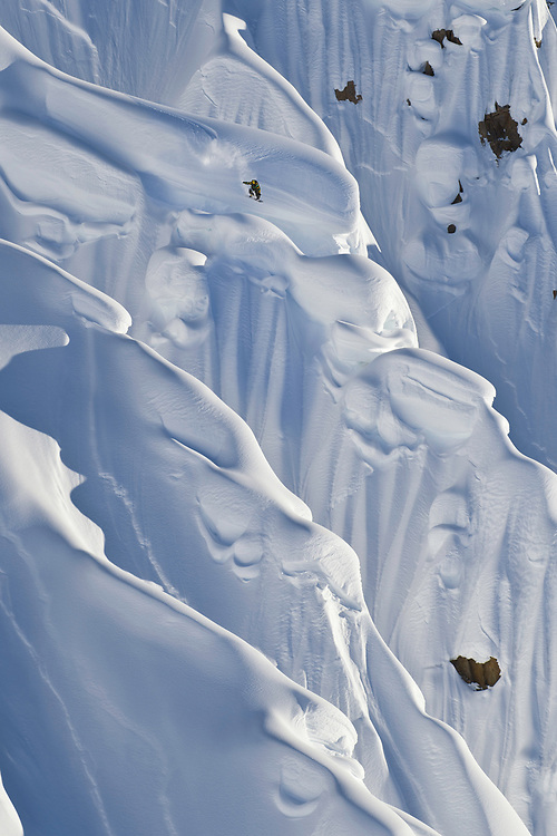 """The Tordrillo Mountains are a small range in the south central region of Alaska. They lie approximately 120 km northwest of Anchorage and are primarily volcanic, which may be what makes them so perfect for snowboarding. On a recent trip there, accompanied by two of the best riders in the world, I was able to photograph the best, most progressive backcountry snowboarding to date. John Jackson blew my mind with his ability to ride such large descents and land obnoxious, oversized airs.<br /> <br /> This photo was taken on a large facing wall, known as Avocado. Half of it gets morning light, while the other half gets evening light. It was late in the day when John spotted a line just about to be blessed with light. The helicopter set me down on an adjacent peak and then dropped him in place to initiate this opportunity. John dropped in, having only seen this line from the air for a few second, and made a few turns before heading right to this cruise-ship sized pillow.<br /> <br /> I remember thinking to myself, """"Oh God, does he know what he is headed for?"""" It's very easy to lose track of where you are, when amazingly huge mountains are all that surround you. One wrong turn can be deadly. Turns out he knew exactly what he was doing and where he was going."""