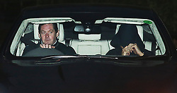 © Licensed to London News Pictures. 17/12/2015. Cobham, UK. A person believed to be Jose Mourinho (R) covers up as he leaves Chelsea FC training ground after being sacked.  Photo credit: Peter Macdiarmid/LNP