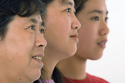 Side view portrait of three generations of a family; grandmother; mother and daughter,