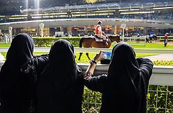 Women in black abayas at parade ring at horse racing meeting at Al Meydan racecourse at night in Dubai United Arab Emirates