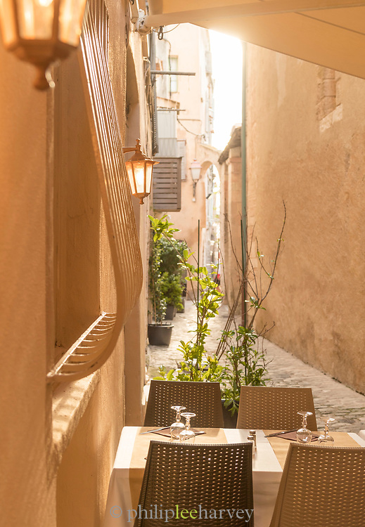 Table on sidewalk in old town between buildings, Bonifacio, Corsica, France