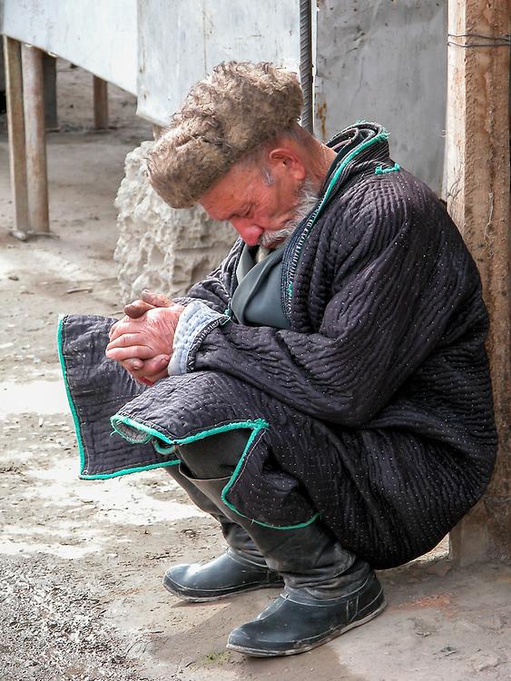 Portrait of an old Tajik man taking a nap in a market in western Tajikistan