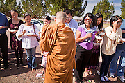 "24 OCTOBER 2010 - CHANDLER, AZ: Ajahn RAYWAT collects rice during the ""tak bat"" or donation of rice to the monks, an important part of Buddhist merit making, during the Ok Phansa services to mark the end of Buddhist Lent at Wat Pa, in Chandler, AZ, Sunday October 24. Buddhist Lent is a time devoted to study and meditation. Buddhist monks remain within the temple grounds and do not venture out for a period of three months starting from the first day of the waning moon of the eighth lunar month (in July) to the fifteenth day of the waxing moon of the eleventh lunar month (in October). Ok Phansa Day marks the end of the Buddhist lent and falls on the full moon of the eleventh lunar month, this year Oct 23. Wat Pa, a Thai Theravada Buddhist temple, celebrated Ok Phansa Day on October 24.    Photo by Jack Kurtz"