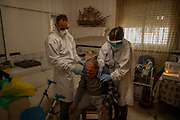 LES ROQUETES DEL GARRAF, SPAIN - APRIL 28: Doctor Lluisa Calvet and nurse Oscar Barba, dressed in a personal protective equipment (PPE), attend to Celestino Navarro during a domiciliary visit on April 28, 2020 in Les Roquetes del Garraf, near Barcelona, Spain. Dr. Lluisa Calvet is monitoring over 60 coronavirus patients who are recovering or decided to stay at home a on daily basis. Domiciliary primary health care doctors are doing a crucial task filtering and monitoring COVID-19 patients to protect Spanish hospitals from being over-crowded. Spain has had more than 232,000 confirmed cases of COVID-19 and over 23,000 reported deaths, although the rate has declined after weeks of lockdown measures.