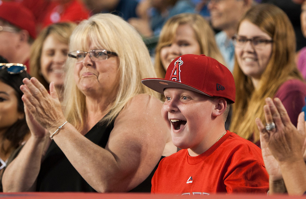 An Angel fans looks pretty happy after getting a baseball from Mike Trout in the on deck circle during the Angels' 5-4 loss to the Oakland Athletics at Angel Stadium on Thursday.<br /> <br /> ///ADDITIONAL INFO:   <br /> <br /> angels.0624kjs  ---  Photo by KEVIN SULLIVAN / Orange County Register  --  6/23/16<br /> <br /> The Los Angeles Angels take on the Oakland Athletics Thursday at Angel Stadium.<br /> <br /> <br />  6/23/16