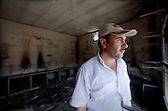 In the burnt ruins of his shop, a villager from Basheria, Idlib, surveys the repair work needed in order to reopen. On April 22nd 2012 the Syrian army and shabiha loyal to Bashar al-Assad attacked the village, killing fifteen, and leaving homes burning and the village petrified for the next attack. 14/06/2012