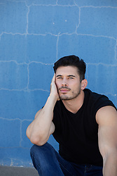 hunky man with light blue eyes against a blue wall