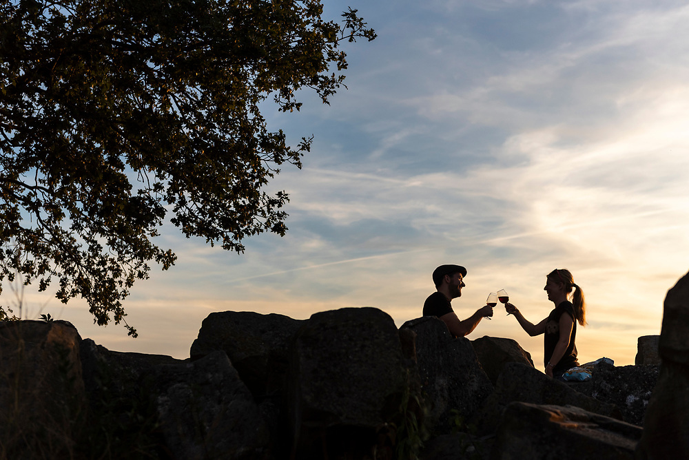 Stuttgart, Germany - August 11, 2018: A couple drinks wine at sunset at the Birkenkopf, a 511-meter high hill in Stuttgart, Germany. Much of Stuttgart was destroyed by Allied bombing during WWII, and in the 1950s rubble was carried to the top of this hill, increasing its height by around 40 meters.