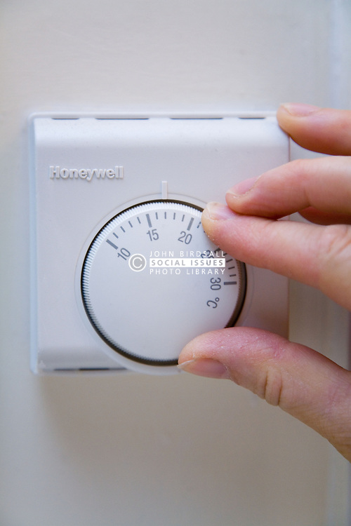 Thermostat on the wall being turned down,