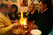 """Tourists share a grilled """"chourico"""" (chorizo) at""""Tasca do Chico"""". This one of the typical spots were to see live perfomances of Fado music and were the audience can spontaneously participate and also ask to sing. It is located in  Bairro Alto neighborhood"""
