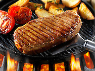 Sirloin beef steaks , tomatoes & chips being pan fried on a bbq. Meat food photos, pictures & images.