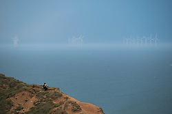© Licensed to London News Pictures.01/07/15<br /> Saltburn by the Sea, UK. <br /> <br /> A woman sits on a rocky outcrop reading a book as a brooding thunderstorm passes over the offshore wind farm off the coast of Teesside and heads out into the north sea after what has been one of the hottest days so far this year.<br /> <br /> Photo credit : Ian Forsyth/LNP