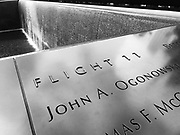 "Black and white photo of a section of the 9/11 Memorial in New York City showing the words ""Flight 11"""